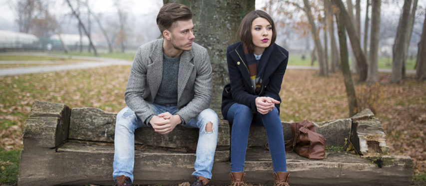 Unhappy couple sitting on bench